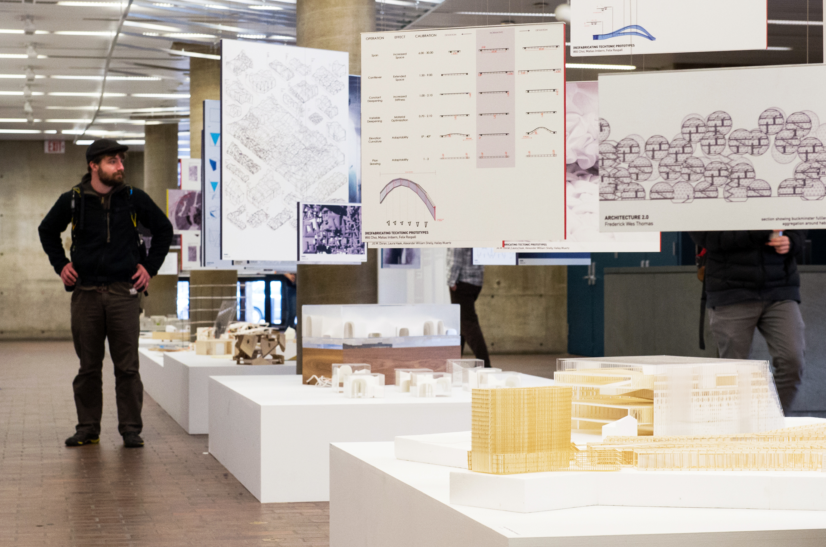 A student passes through a recent exhibition featuring urban planning and design projects