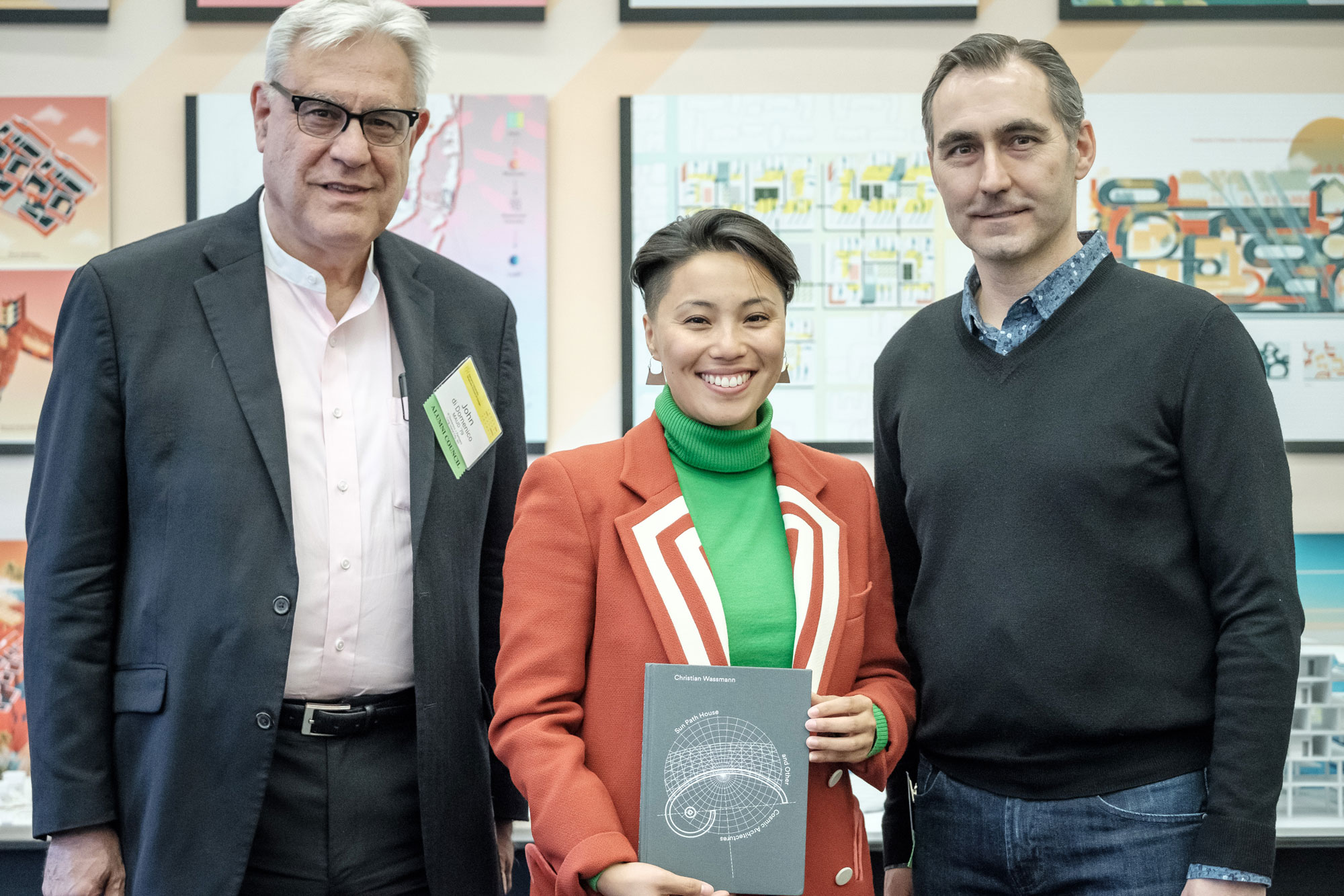 Natalie Wang MDes '19 with her book selection Sun Path House and Other Cosmic Architectures by Christian Wassmann and Hendrik Schwantes. She is photographed with Alumni Council members John di Domenico MAUD '79 (left) and Chris Bourassa AMDP '09 (right).