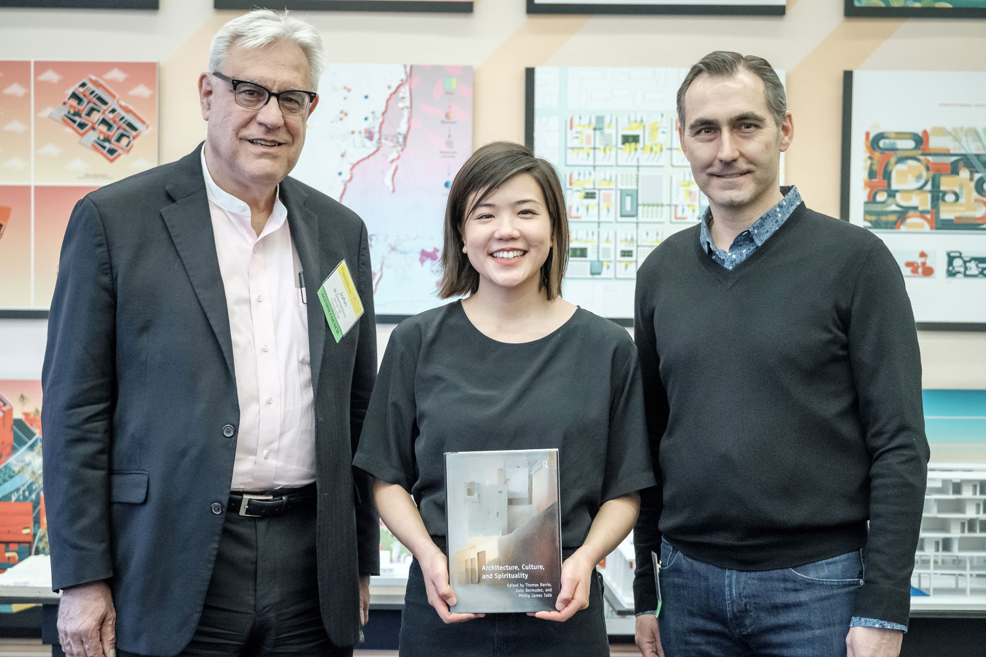 Chantine Akiyama MArch '19 with her book selection Architecture, Culture, and Spirituality by Thomas Barrie and Julio Bermudez. She is photographed with Alumni Council members John di Domenico MAUD '79 (left) and Chris Bourassa AMDP '09 (right).
